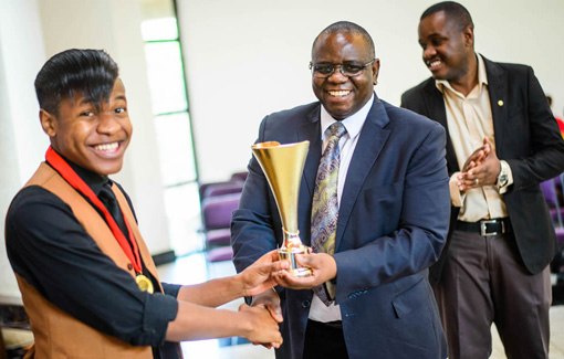 Fosters student president received trophy from Vice Chancellor Furusa.
