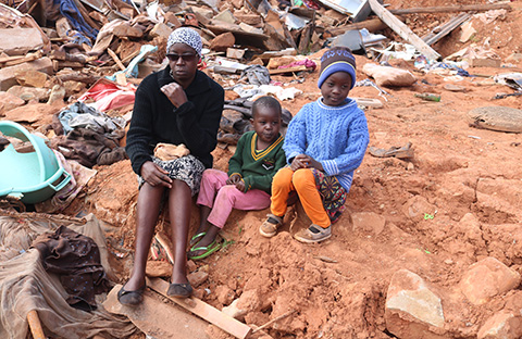 Emily Giwa and her two younger children sit amidst boulders and the remants of household goods in cyclone-ravaged Nyangu Township