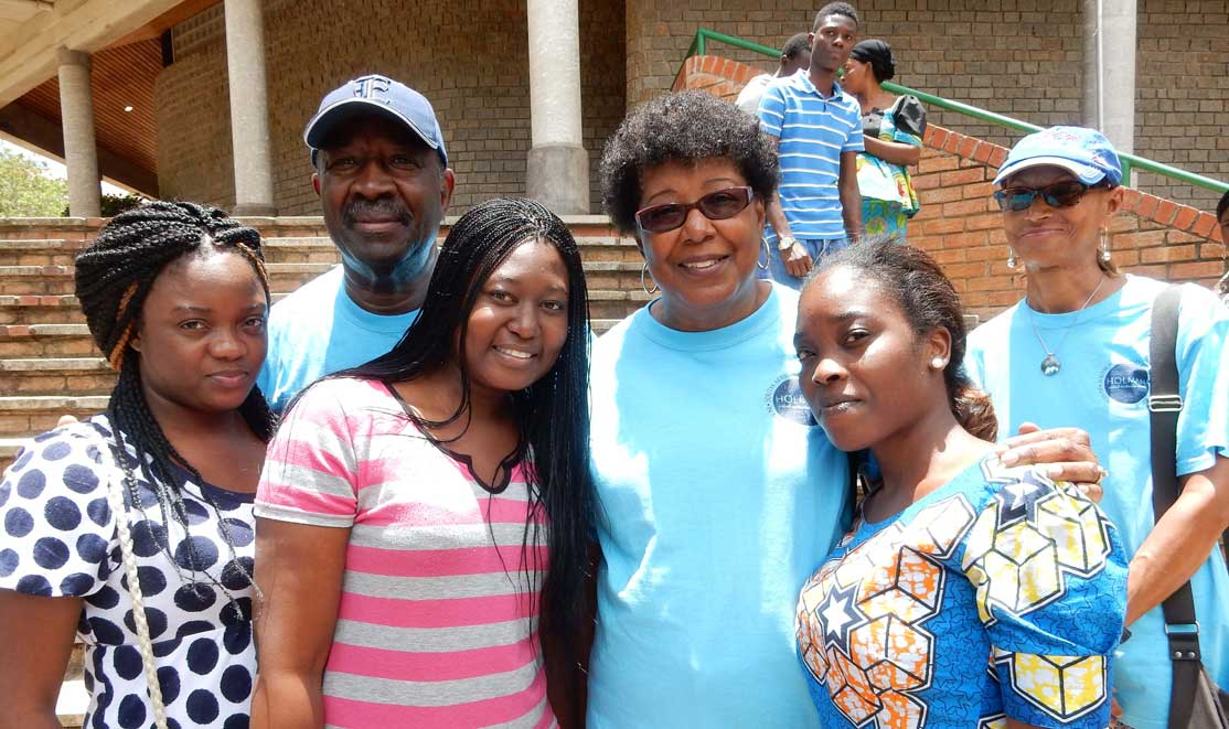Sandrel and Edward Terry with students on the campus.