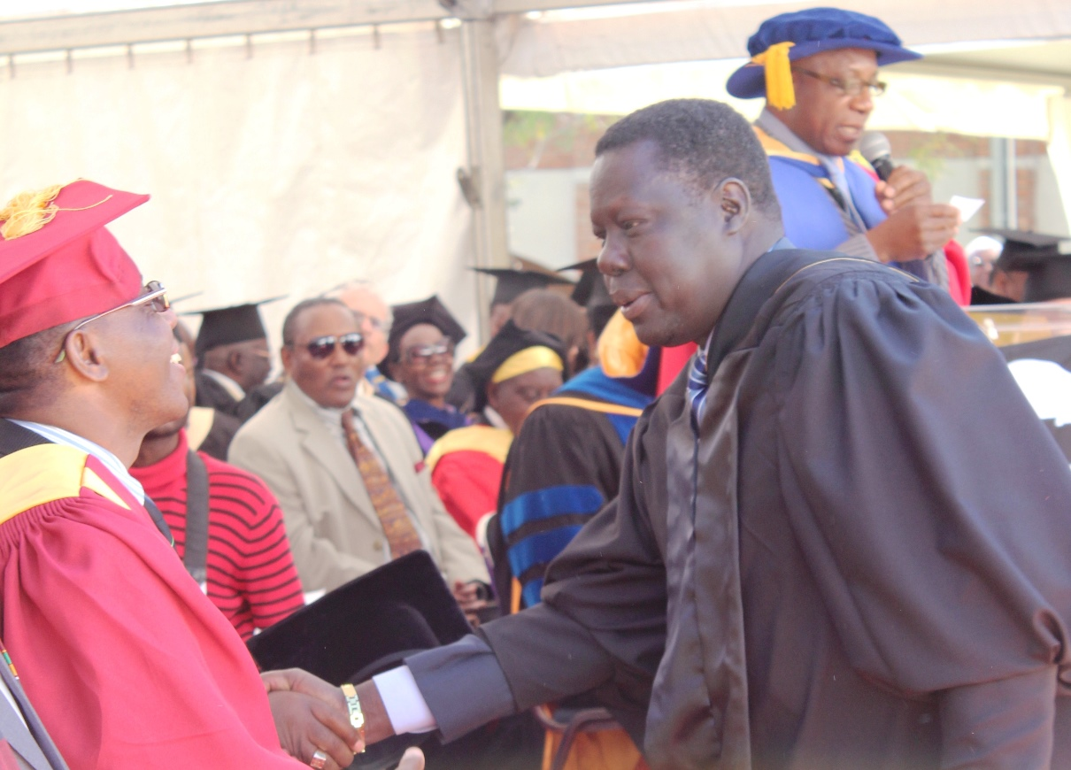 A Handshake and congratulations for Ambassador Boutros Thok Deng of South Sudan, from Dr.Timothy Simalenga, the 2014 commencement speaker.